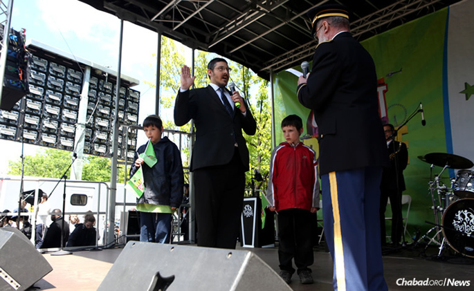 """Rabb Yossi Madvig, left, """"solemnly affirmed"""" his commitment to the U.S. Army Reserve as a new chaplain on May 14 in Brooklyn, N.Y. Presiding over the ceremony was U.S. Army Col. (ret.) Jacob Goldstein. Two of Madvig's children joined him onstage: Menachem Mendel, left, and Levi Yitzchok."""