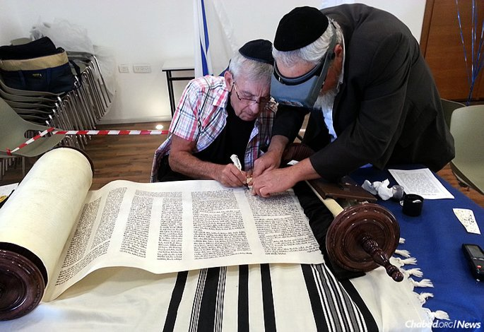 A man who fought in the Six-Day War writes a letter in a Torah scroll just completed in Efrat, Israel. (Photo: Bais Yisroel Torah Gemach)