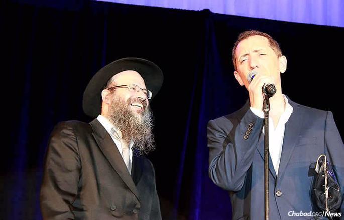 Lors d'un spectacle à Montréal en mai 2017, le comédien Gad Elmaleh a évoqué son séjour au Camp Tsivot Hachem dans son Maroc natal, où il a développé une relation chaleureuse avec le rabbin Leibel Raskin et où s'est exprimé son humour précoce. Ici, Gad Elmaleh partage un moment avec le fils du rabbin, Rav Mendel Raskin, qui codirige le Beth Chabad CSL, où s'est tenu le spectacle.