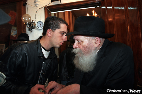 Gad Elmaleh receiving a dollar and a blessing from the Rebbe.