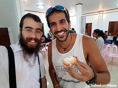 The rabbi and a new friend enjoy a jelly doughnut (homemade, of course) at Chanukah.