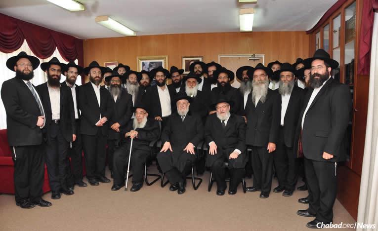 Rabbi Yisrael Meir Lau, Tel Aviv's chief rabbi, is seated at center, with Rabbi Sholom Ber Butman at left and Rabbi Yosef Gerlitsky at right, surrounded by fellow Chabad-Lubavitch rabbis who serve the city of Tel Aviv.