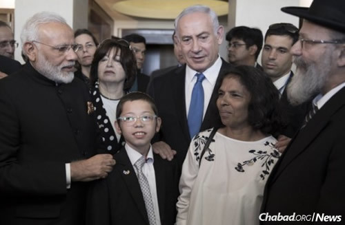Moshe Holtzberg thanks Sandra Samuel, second from right, for saving his life as Prime Minister Narendi Modi of India and Prime Minister Benjamin Netanyahu of Israel look on. Joining them are Moshe's maternal grandmother, Yehudit Rosenberg, and his paternal grandfather, Rabbi Nachman Holtzberg, right. (Photo: AFP Photo/Pool/Atef Safadi)