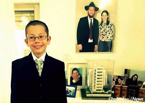 With photographs of his parents, Rabbi Gavriel and Rivka Holtzberg, and Sandra Samuel, the Indian nanny who saved his life.
