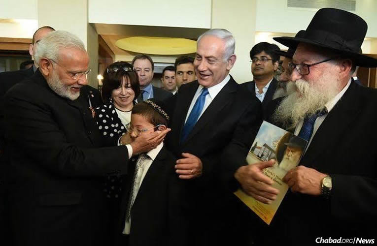 Prime Minister of India Narendra Modi meets Moshe Holtzberg, who survived a 2008 terrorist massacre in Mumbai that took the lives of his parents, Chabad-Lubavitch emissaries Rabbi Gavriel and Rivka Holtzberg. Among those looking on are Moshe's paternal grandmother, Fraida Holtzberg; Prime Minister Benjamin Netanyahu of Israel; and Moshe's grandfathers, Rabbi Nachman Holtzberg, second from right, behind Rabbi Shimon Rosenberg, right.