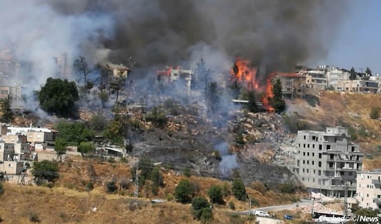 Raging brush fires fueled by sweltering midsummer temperatures and high winds swept through a neighborhood on the northern edge of the historic spiritual center in Israel's Galilee, leaving families homeless.