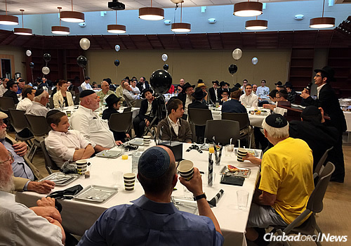 The room full of boys and guests. The goal was to honor the 50th year since the launch of the Tefillin Campaign by the Lubavitcher Rebbe, Rabbi Menachem M. Schneerson.