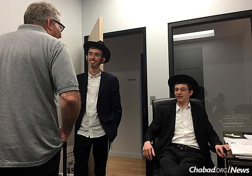 Ari Oirechman and Motti Slonim talk with Mark Warren, who's on their regular route.