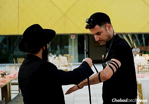 Local yeshivah students help guests don tefillin. (Photo: Avraham Edery)