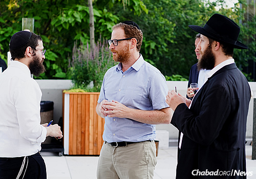 Rabbi Ahrele Loschack, left, and Rabbi Mordechai Lightstone chat with an event attendee. (Photo: Avraham Edery)
