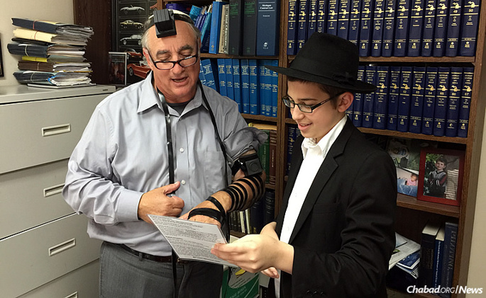 """Shmuli Marozov, a student at Lubavitch Yeshivah-Zekelman Campus in Oak Park. Mich., helps Anthony Kahn put on tefillin at work. The """"Friday boys,"""" as they are called, surpassed a goal of wrapping tefillin with 1,000 men in two months; instead, they reached nearly 1,350."""