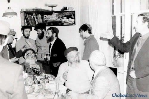 A Jewish gathering in Moscow in the early 1980s. Reb Getche Vilensky is seated at the head of the table; to his right is refusenik Vladimir Slepak, who spent 17 years trying to receive an exit visa. (Photo courtesy of Association Remember and Save)
