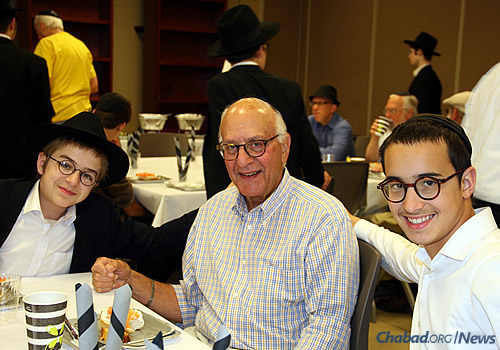 "Shea Shmotkin and Sholom Schonbuch sit with Jerry Eisenshtadt at a Sunday brunch celebrating the efforts of the ""Friday boys."""