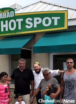 Rabbi Yaakov Raskin, center, with diners (Photo: Chabad of Jamaica)