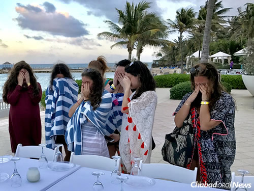 Women say the blessing over the candles before a Shabbat celebration on the beach. (Photo: Chabad of Jamaica)