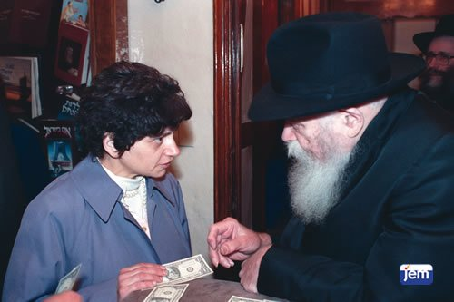 Yehudis Fishman receives a dollar from the Rebbe decades after the meeting recalled in the book.