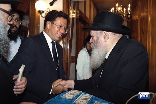 Yossi Ben Hanan receives a dollar from the Rebbe.
