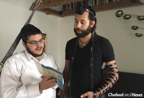 Caspar, right, celebrates his bar mitzvah after putting on tefillin for the first time, at age 47, with rabbinical student Levi Loewenthal.