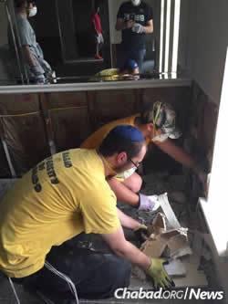 Rabbi Ezra Wiemer works alongside Colorado University freshman Ryan Spitzer, tearing off flood-damaged drywall.