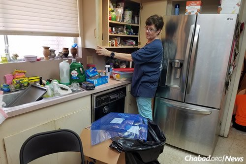 "Susy Brown, who was rescued as the floodwaters rose, says ""the volunteers have been amazing! We have kosher meals delivered, and a team of young people to work with me and my children as we salvage our home."""