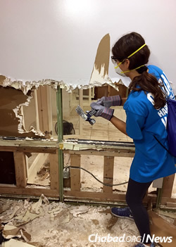 Knocking out sodden drywall in a home (Photo: Elisheva Golani)