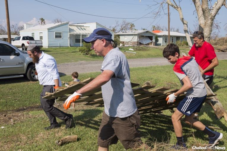 Schmukler, left, is accompanied by volunteers Dr. David Ryan, center left, Alex Ryan and Mitch Stuart, far right, who work to remove debris from a local home in Rockport. (Photo: Verónica G. Cárdenas/Chabad.org)