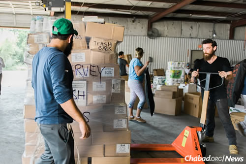 Jewish community volunteers help unload food and aid arriving from New York at Chabad-Lubavitch of Texas Regional Headquarters . Five trucks of kosher food and other goods have so far come from Miami via Dallas and New York, with at least another six trucks on the way. (Photo: Elisheva Golani/Chabad Harvey Relief)
