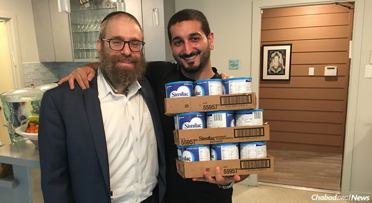 Rabbi Chaim Lazaroff, left, co-director of Chabad of Uptown, hands containers of baby formula to a father in Houston. Chabad-Lubavitch Texas Regional Headquarters has been coordinating rescue and relief efforts since the start of Hurricane Harvey.