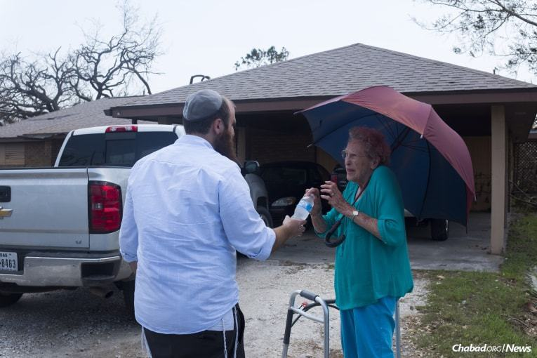 Schmukler brings water to a woman affected by Hurricane Harvey in Rockport. (Photo: Verónica G. Cárdenas/Chabad.org)