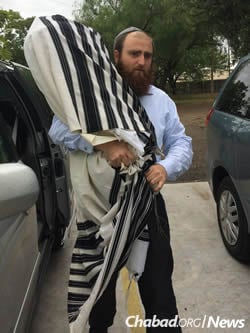 Rabbi Naftali Schmukler of Corpus Christi takes a Torah scroll to safety after being ordered to evacuate on Friday.