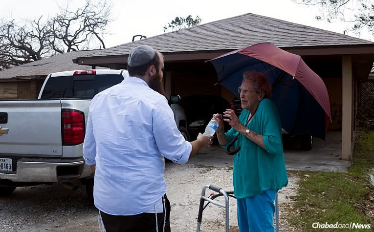 Chabad-Lubavitch Rabbi Naftoli Schmukler, left, of Corpus Christi, Texas, brings bottled water to a woman affected by Hurricane Harvey in Rockport, Texas. A contingent of 50 rabbis from across the United States is heading to the beleaguered state to counsel and comfort struggling residents. (Photo: Verónica G. Cárdenas/Chabad.org)