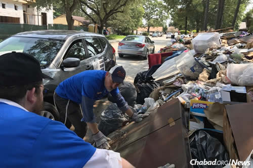 Rabbi Yossel Kranz of Chabad of Virginia in Richmond helps homeowners clean out debris.