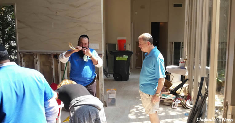 Rabbi Mendy Rubenfeld of Poway, Calif., blows the shofar for disaster victims and volunteers in Houston. He is one of 50 rabbis from a dozen states helping out spiritually and materially in homes, shelters and hospitals.