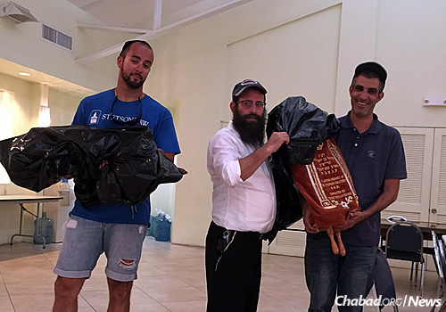 Rabbi Yaakov Zucker, center, co-director of Chabad Jewish Center of the Florida Keys, gets some help covering and moving Torahs to a safe place.