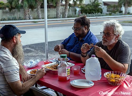Rabbi Tzvi Konikov, left, co-director of Chabad of the Space & Treasure Coasts in Satellite Beach, Fla., invites local residents to a free barbecue on Monday. (Photo: Chavi Konikov)