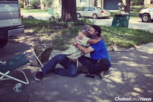 Rabbi Yossi Lipsker, director of Chabad Lubavitch of the North Shore in Swampscott, Mass., and co-founder of 1Mitzvah, the organization sponsoring the mission, hugs a homeless man in Houston.