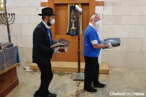 Retreiving for burial ruined holy books from the United Orthodox Synagogue, which was severely damaged in the flooding.