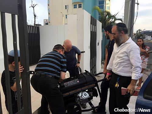 Providing generators to assist community members, overseen by Rabbi Zarchi, at right.