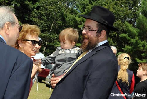 The rabbi with the youngest member of the family, Devorah Leah Freeman