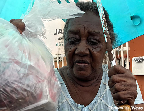 A woman accepts a bag of items.