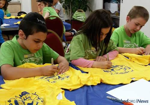 Kids at Camp Gan Israel decorate T-shirts.