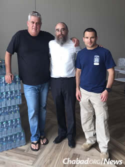 Rabbi Mendel Zarchi, center, and Jewish community members with bottled water on hand for the storm and its aftermath.