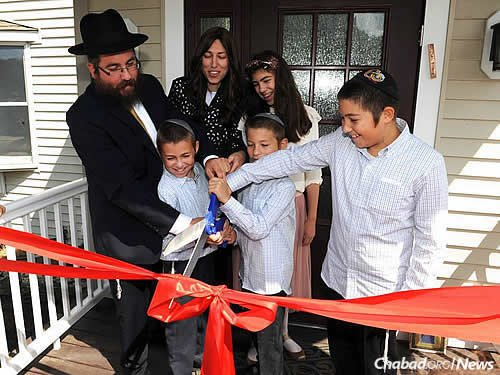 Four of the five Freeman children help cut the ribbon. Bottom, from left: Mendel, Zalman and Levi, with Chana in the back.