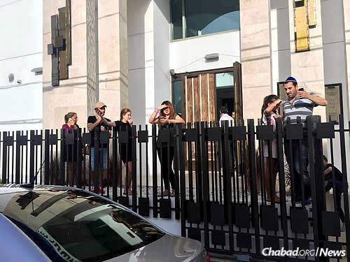 People gather outside Chabad of Puerto Rico to attempt cell-phone connections.