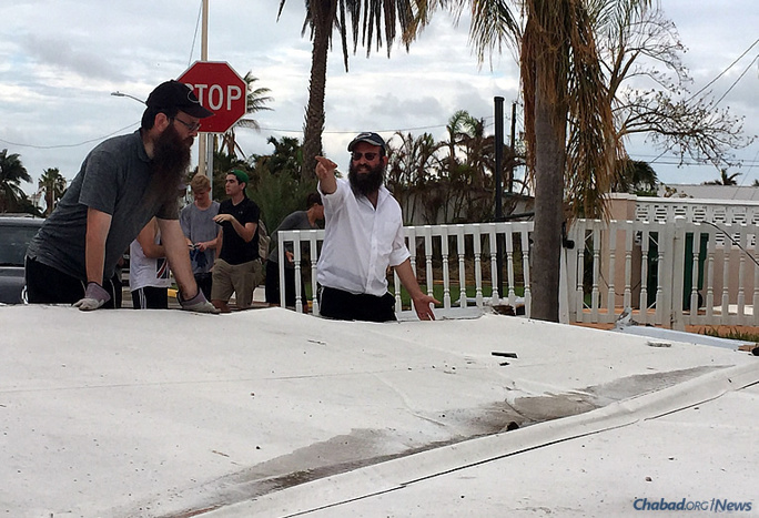 Rabbi Yaakov Zucker, right, co-director of the Chabad Jewish Center of the Florida Keys and Key West, helps lead cleanup efforts for Jewish residents who have returned to their homes after Hurricane Irma and before the High Holidays. He has gotten assistance from other South Florida-based rabbis, as well as a group of young volunteers on Tuesday.