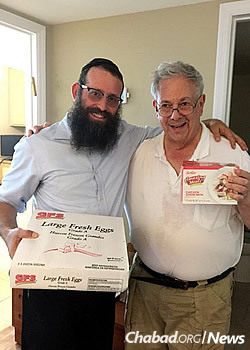 The rabbi with local resident Syd Wharton, handing out kosher food. Chabad is also hosting meals before and after Yom Kippur for community members.