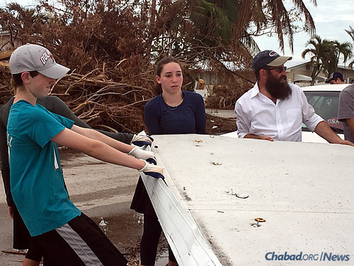 Teens from Jewish day schools haul soiled mattresses away and pick up strewn debris.