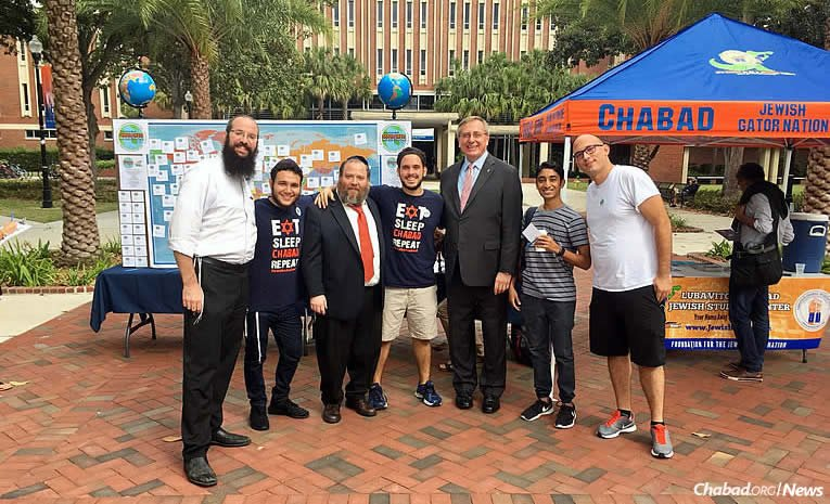 Rabbi Aharon Chaim Notik left co-program director at the Tabacinic Lubavitch Chabad Jewish Student Center at the University of Florida in Gainesville Rabbi Berl Goldman third from left co-director of the Chabad center and university president Kent F