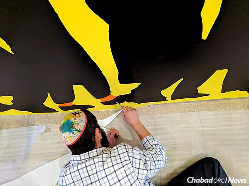 """In Jerusalem for the grand opening on Oct. 11, Moully puts the finishing touches on his """"Orange Socks"""" mural."""