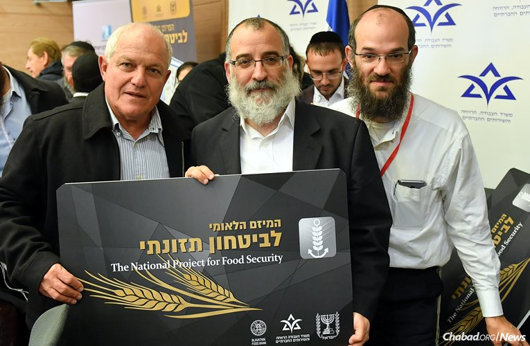 """Through a series of new workshops focusing on healthy cooking and eating, Colel Chabad is emphasizing more nutritional fare for Israel's poorest residents. Holding up an """"Eshel"""" card used to purchase food from supermarkets are, from left, Israel's Minister of Welfare Haim Katz; Rabbi Mendy Blau, Israel director of Colel Chabad; and Colel Chabad food program director Tzvi Blau. (Photo: Colel Chabad)"""